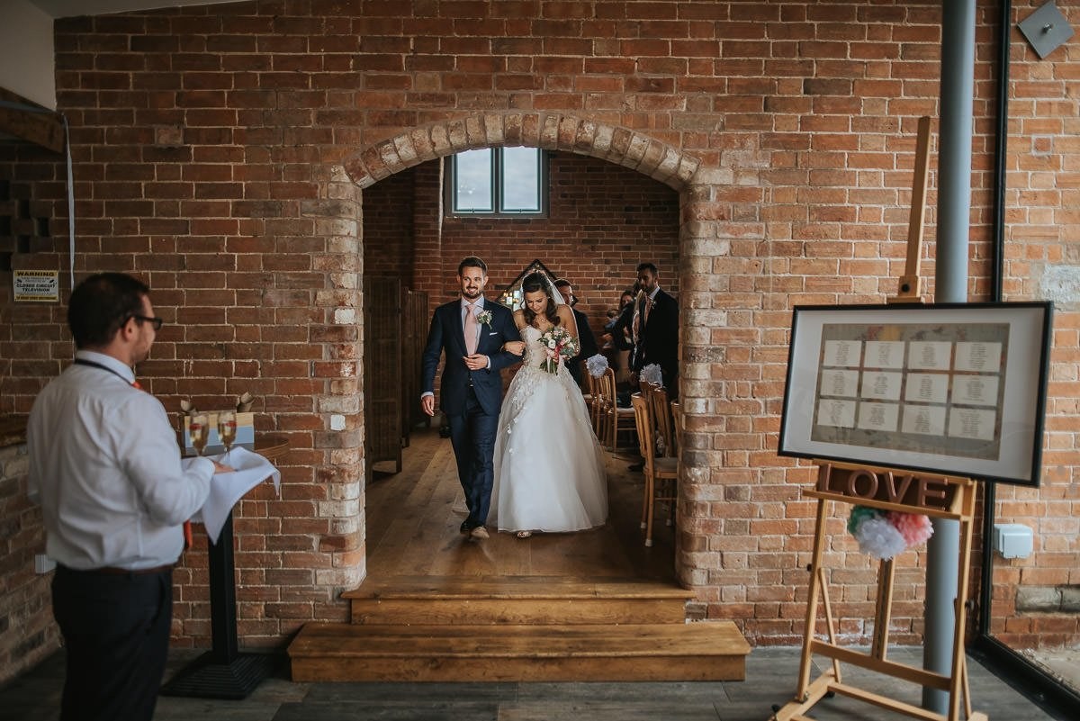 swallows nest barn newlyweds coming out from the ceremony room