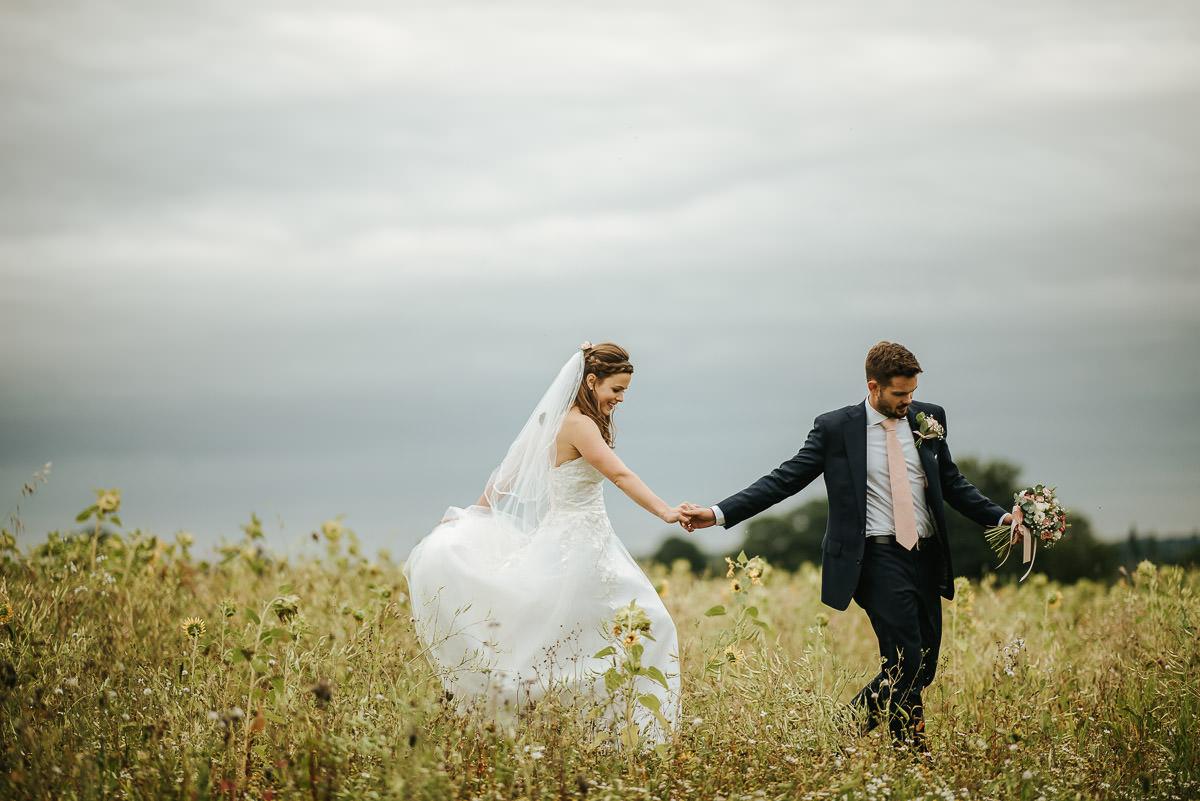 swallows nest barn wedding couple running through a field of sunflowers
