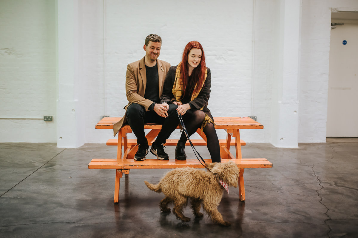 couple in brick lane on a bench with a dog