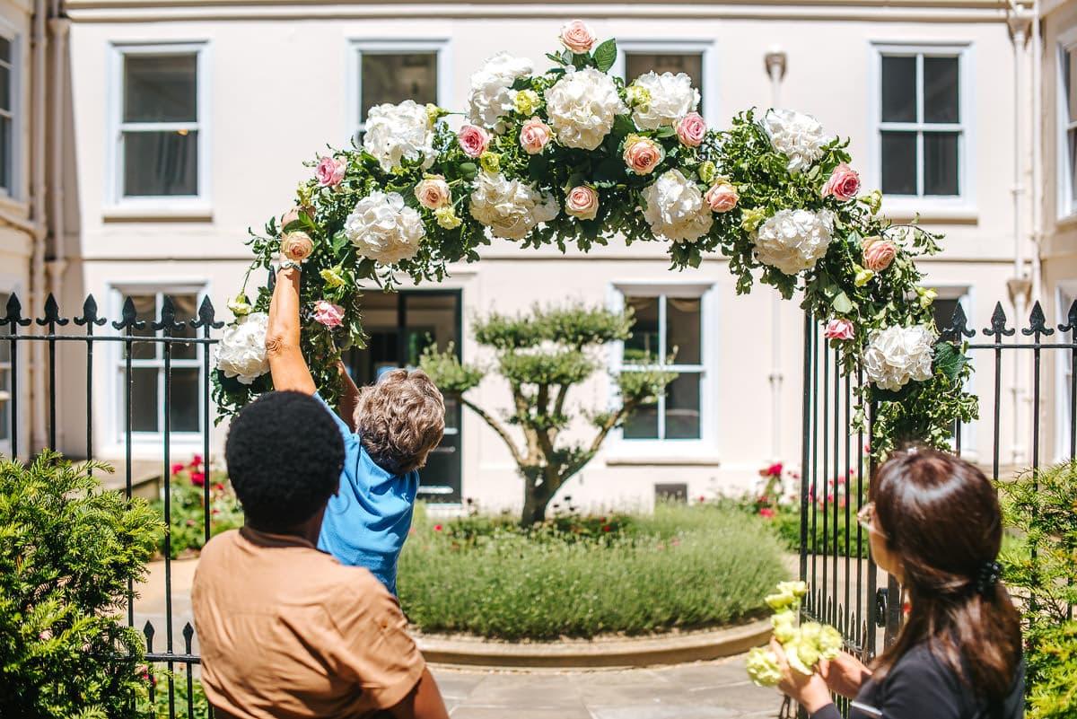guestts preparing flower arch, wedding decoration idea
