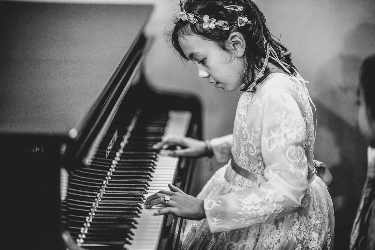 chinese girl playin piano at a wedding in hall place in london