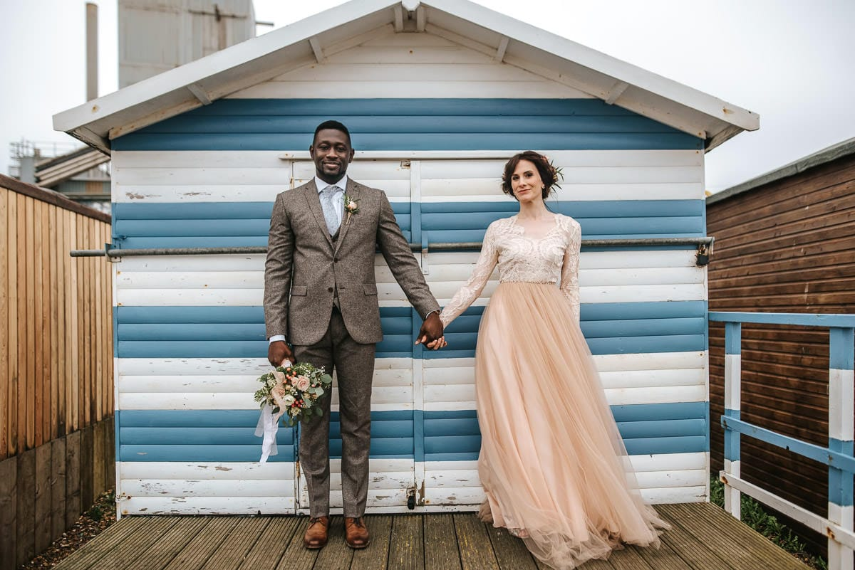 east quay venue wedding bride and groom by the beach huts
