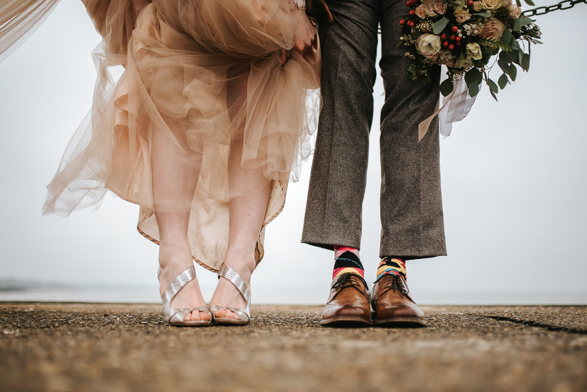 east quay venue wedding bride and groom by the pier shoes