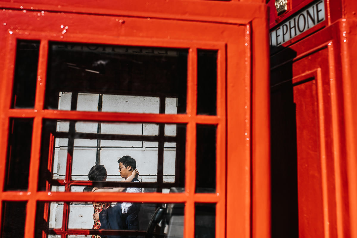 london engagement photography covent garden embracing next to red phone booth