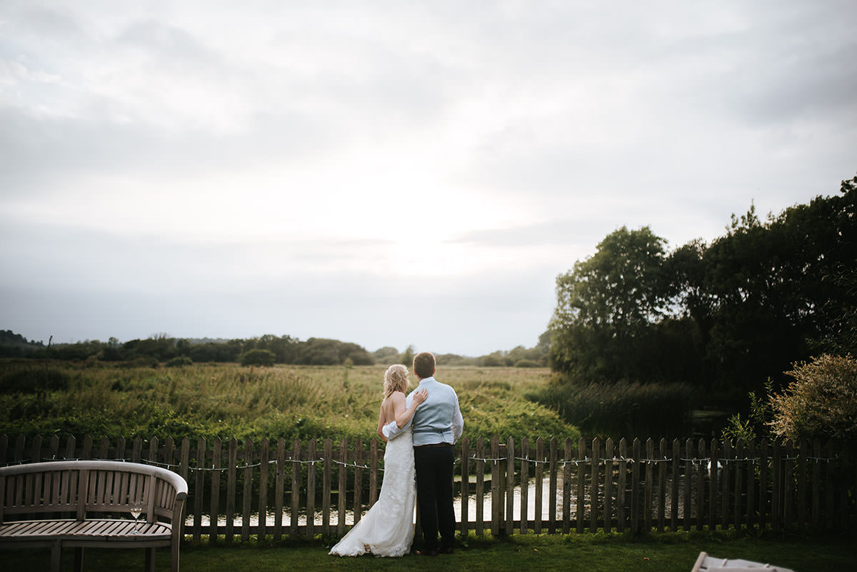 sopley mill wedding bride and groom standing and looking into the sunset